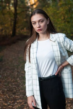 Portrait of a young beautiful girl on the background of autumn,