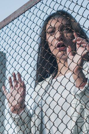 Girl holding hand on metal chain wire mesh, concept of abuse of women human trafficking, crime and domestic violence,