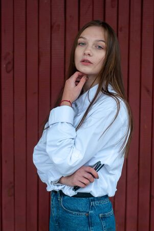 A girl posing against a red background, a young model in a white shirt and with long straight hair, Stok Fotoğraf
