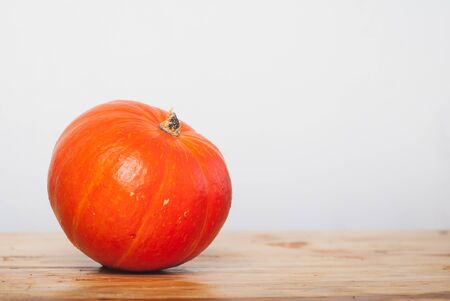 Pumpkin on a wooden table against a white wall, pumpkin minimal