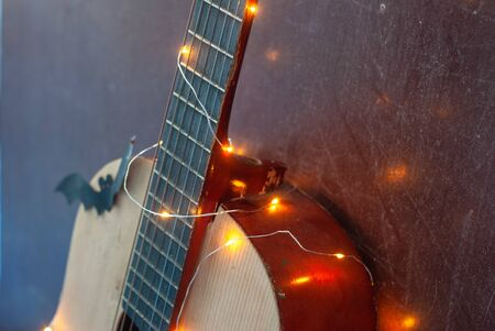 acoustic guitar in yellow garland light, festive background