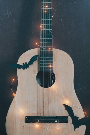 Acoustic guitar in autumn season. guitar with garland and bat. Concept sale of guitars on Halloween and black Friday