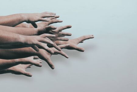 Lots of zombie hands on light background. Hands will reach out. The concept of discounts on the day of black Friday