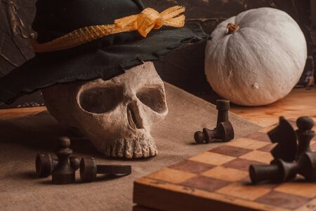 Composition for Halloween with skull and white pumpkin and chess. The concept of a deadly game