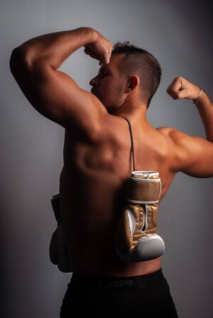 Tanned boxer posing against the wall. Muscular back