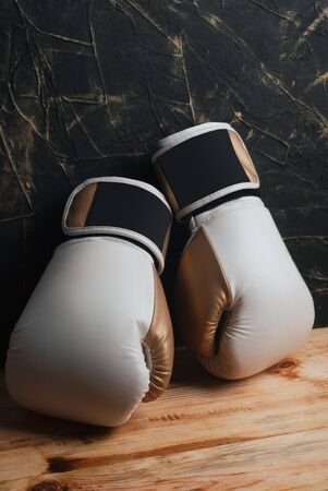 Boxing white gloves and a wooden table with a black wall.