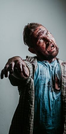 The zombie reaches out a bloody hand trying to reach.