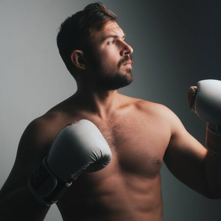 A boxer in a white Boxing glove poses on a light background