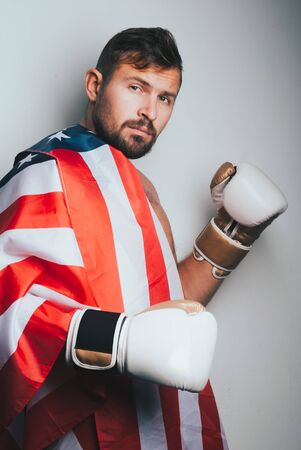 Portrait of happy man with the American flag, a boxer with white gloves after winning
