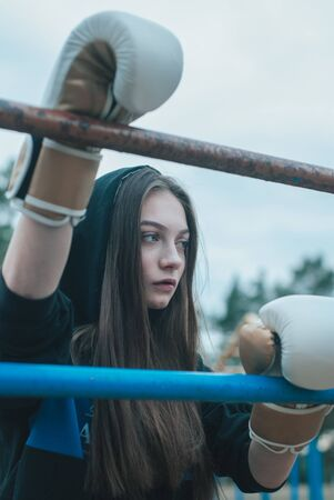 the girl with long hair in Boxing gloves in the open air. The concept of a strong girl