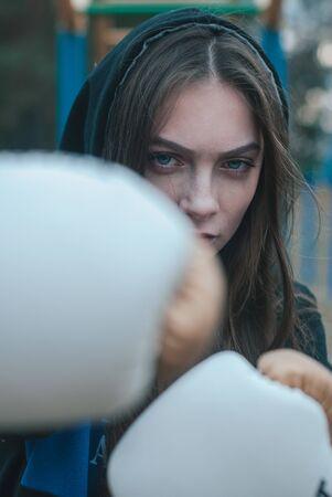 Boxer girl outdoors. The concept of a strong girl