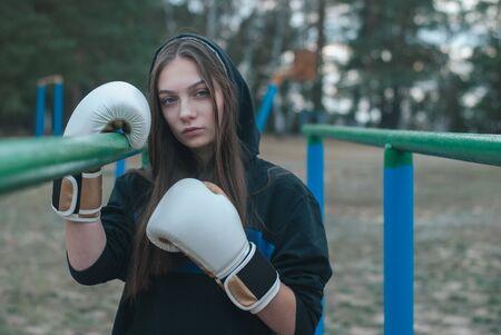 Boxer girl outdoors. The concept of a strong girl,