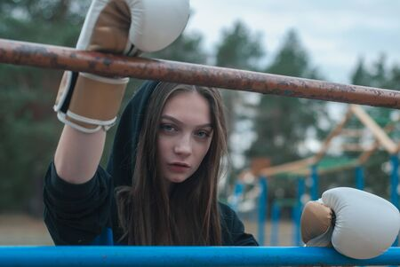 the girl with long hair in Boxing gloves in the open air. The concept of a strong girl,