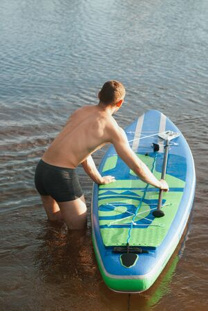 Slim guy on the sup Board. the view from the back,
