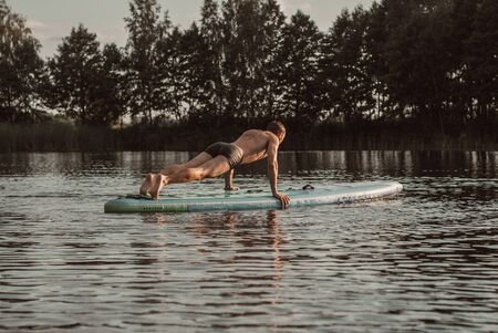 A young guy makes a plank on a sup Board. SUP yoga, Stock Photo