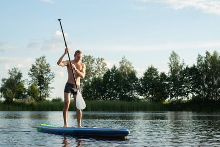 Guy doing paddle boarding on lake, lucky man on SUP Board, Stok Fotoğraf