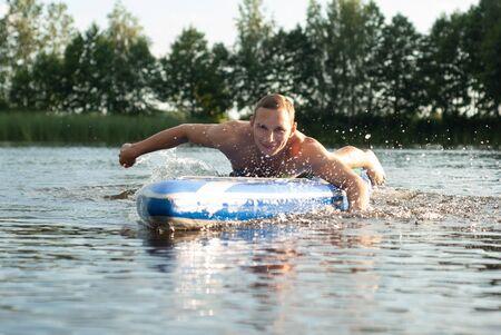A young surfer paddles hands portrait. active lifestyle