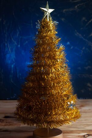 Yellow Christmas tree on a blue background, Christmas tree with a star