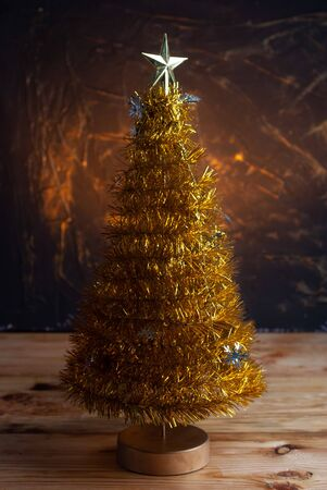 Yellow Christmas tree on a yellow background, Christmas tree with a star on the table