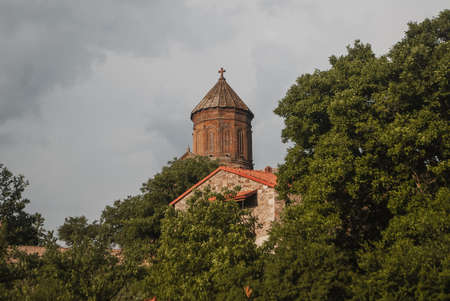 The tower of the temple among the trees, an ancient monastery, Stockfoto