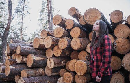 Hipster tender girl on the background of felled trees,