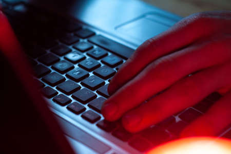 a man working in a laptop close-up, hands on the keyboard, Stock Photo