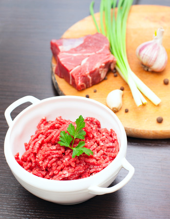 Minced meat in a white bowl with fresh herbs and spices on a desk  photo