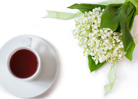 bouquet of lilies and cup of tea, isolated on white photo
