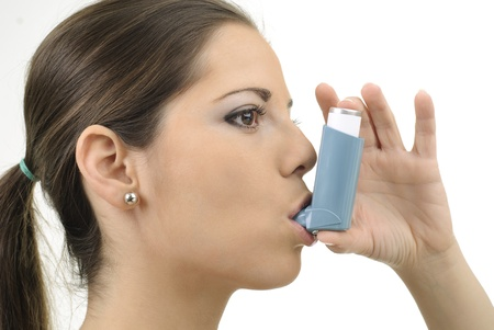 asthma: young women with asthma inhaler