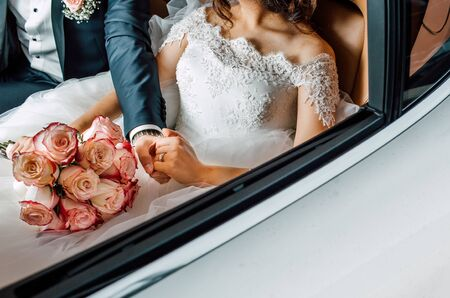 A wedding couple sitting in auto and holding each others hand, flowers in hand