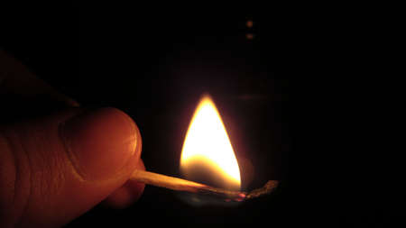 Close up of a man's hand lighting a single match in the dark Imagens