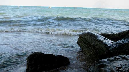 Sea water waves hits the coast rocks with high pressure in a public beach Foto de archivo