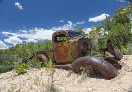 Rusted and corroded old car grown into the landscape near Bryce Canyon, Arizona, United States of America