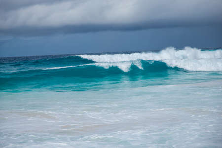 Turquoise ocean waves with dramatic sky on La Digue Island, Seychelles