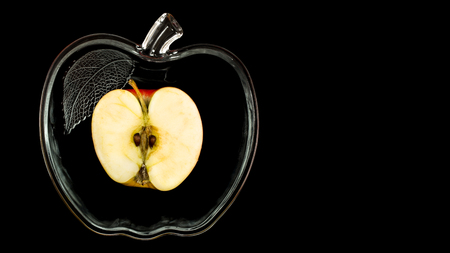 sliced apple in a glass bowl on a black background.