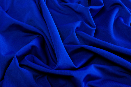 smooth blue satin silk fabric. folds, curl. Satin background.