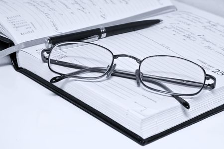 pen glasses and notebook in composition in blue tone photo