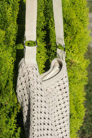 Cream crocheted handbag behind the in the garden in countryside Standard-Bild