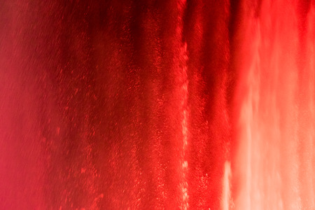 background with a view of the jets from the spray of a large fountain with lights red color