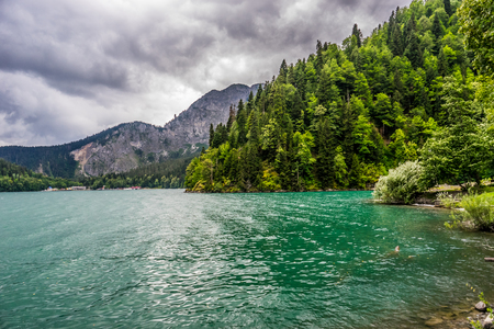 The emerald green lake framed by the forest and mountains in the gloomy rainy weather