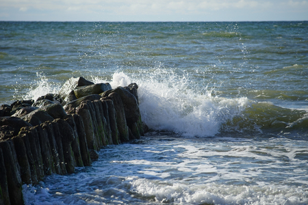 Wave with small white spray crashing against the coastal breakwater at the Baltic sea. Stockfoto