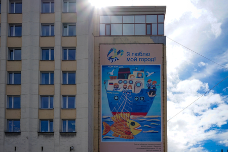 Murmansk, Russia-June 5, 2015: Modern building with big banner with picture background of blue sky and sunlight.