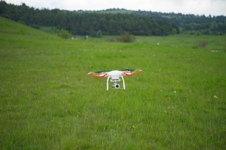 Natural landscape with green grass field under the sky with clouds and quadcopter. Stock Photo