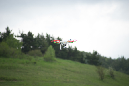 Natural landscape with green grass field under the sky with clouds and quadcopter. Standard-Bild
