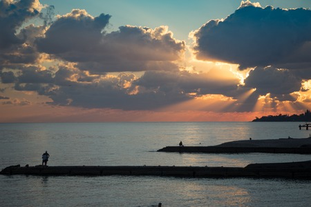 Coastline with beaches, breakwaters and people silhouette against a bright sunset and dramatic sky.