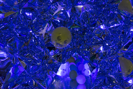 Abstract blue glowing background with facets, reflections and a yellow ball with a smiley face