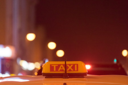 Taxi sign on the roof of the car on a blurred background in red evening light. Фото со стока