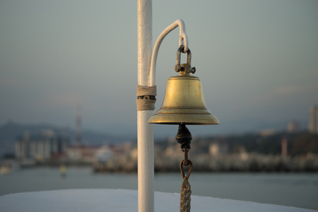 copper bell on the yacht on the background of eroded shoreline