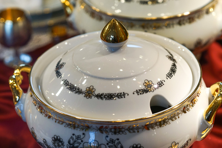Background with white porcelain tableware with floral ornament and gilded details. Stok Fotoğraf