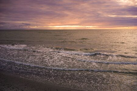 Seascape with a beautiful sunset over the horizon and the water surface.